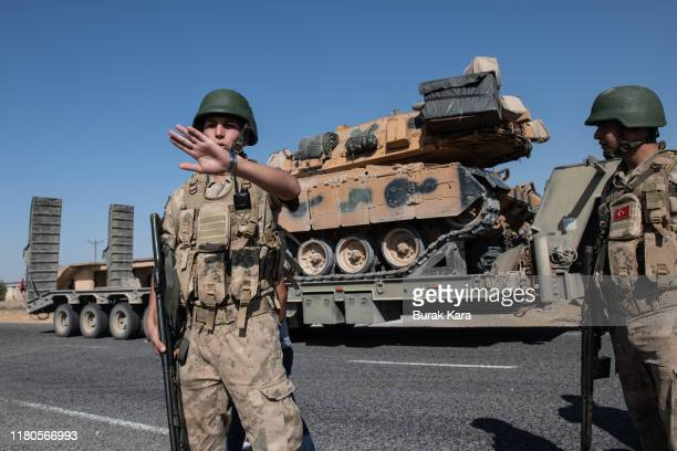 Turkish soldiers secure the area as Turkish military vehicles carry tanks to the Syrian border on October 12 2019 in Akcakale Turkey The military...