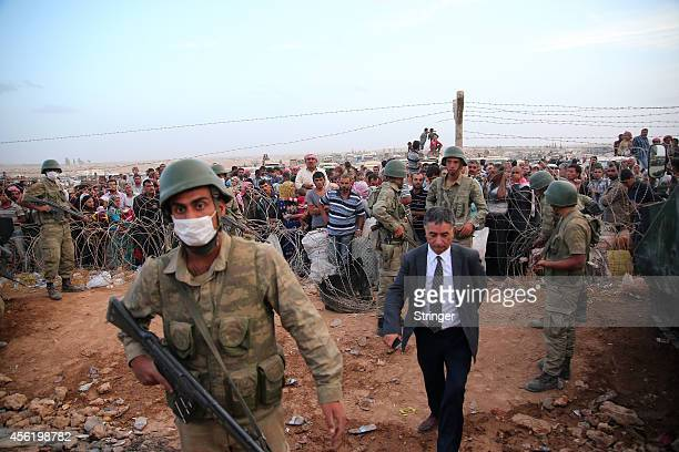 Turkish soldiers stand guard as Kurdish Syrian refugees wait to cross into Turkey on the TurkishSyrian border near the southeastern town of Suruc in...