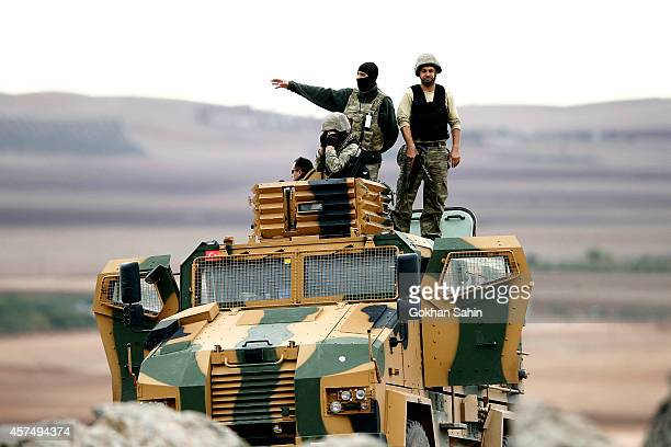Turkish soldiers stand guard as they take up position on top of an APC by the TurkishSyrian border opposite the Syrian town of Kobani as seen from...