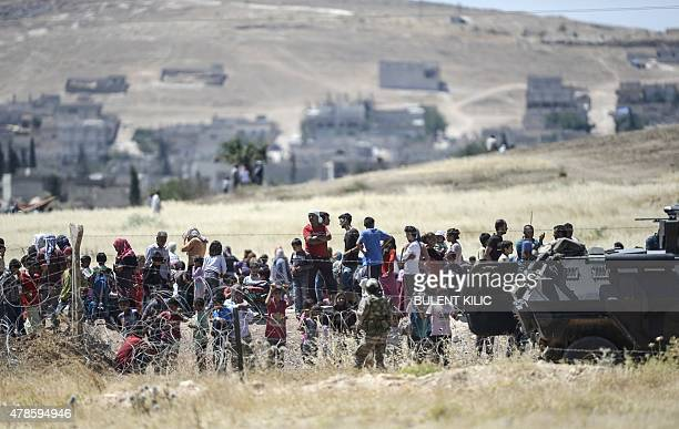 Turkish soldiers stand guard on the Turkish side of the border in Suruc Sanliurfa province as Syrian Kurds wait behind the barbed wired on the Syrian...