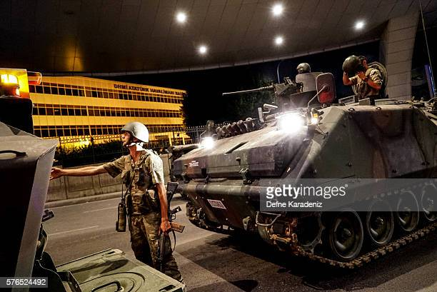 Turkish soldiers stand guarded near army's tanks as they enter the Ataturk Airport on July 16 2016 in Istanbul Turkey Istanbul's bridges across the...
