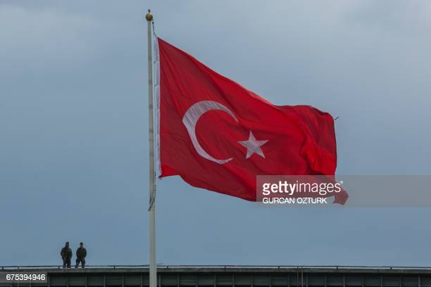Turkish soldiers stand near a Turkish flag in Istanbul on May 1, 2017. - Police tried to stop around 200 protesters in the Gayrettepe district on the...