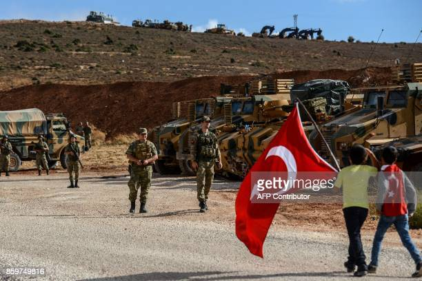 Turkish soldiers stand near armoured vehicles as two young boys holding Turkish national flags arrive during a demonstration in support of the...