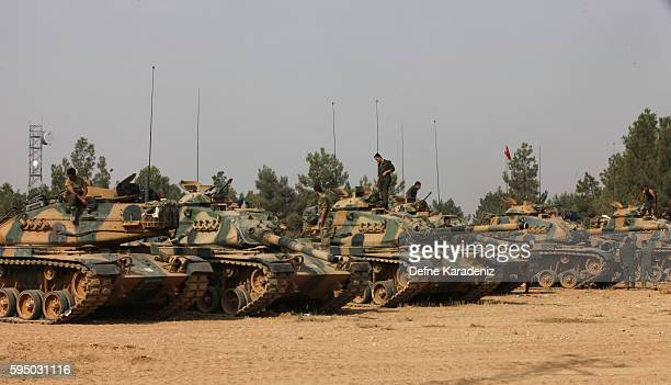 Turkish soldiers stand on tanks as they prepare for a military operation at the Syrian border town of Karkamis in the southern region of Gaziantep on...