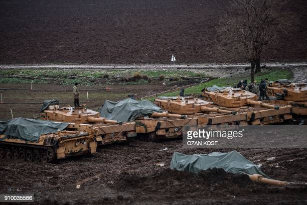 Turkish soldiers stand on their Germanmade Leopard 2A4 battle tanks stationed in a field near the Syrian border at Hassa in Hatay province on January...
