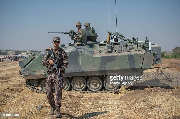 Turkish soldiers take security measures on the Syrian borderline as the construction of the concrete wall on the border continues in the Suruc...