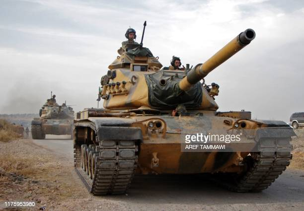 Turkish soldiers with US-made M60 tanks drive through the town of Tukhar, north of Syria's northern city of Manbij, on October 14 as Turkey and its...