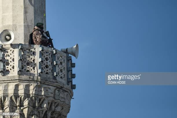 A Turkish special force police officer stands guard on a mosque's minaret during the speech of the Turkish president on December 15 2017 in Istanbul...