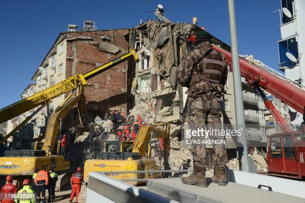 A Turkish Special force stands guard as rescue workers search for survivors in the rubble of a collapsed building after an earthquake hit Elazig...