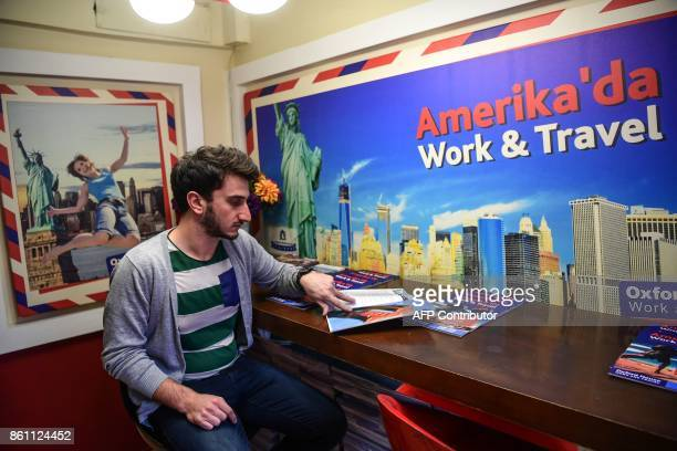 A Turkish student looks at US work and travel brochures at an education travel agency in Istanbul on October 11 2017 Turkish students business...