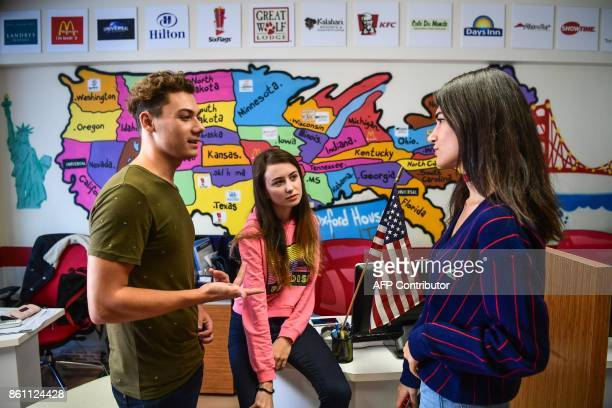 Turkish students chat front of a map of the United States of America at an education travel agency in Istanbul on October 11 2017 Turkish students...