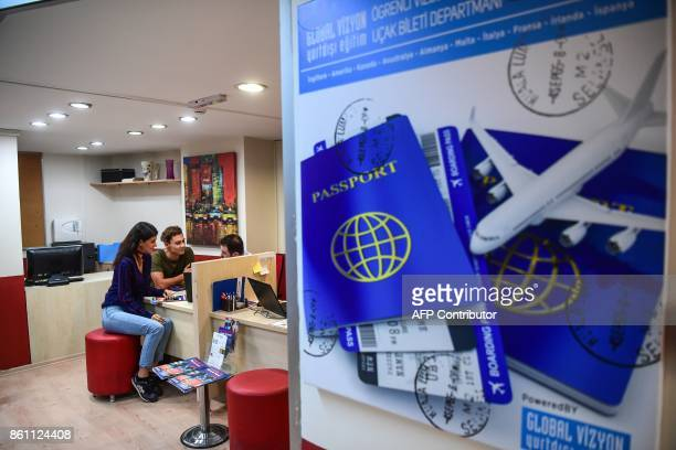 Turkish students inform themselves about US work and travel programs by an adviser at an education travel agency in Istanbul on October 11 2017...