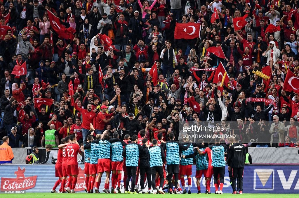 Turkish supporters celebrate with Turkey's team players after wining the UEFA Nations League football match between Sweden and Turkey at the Friends Arena in Solna, on the outskirts of Stockholm, on September 10, 2018.