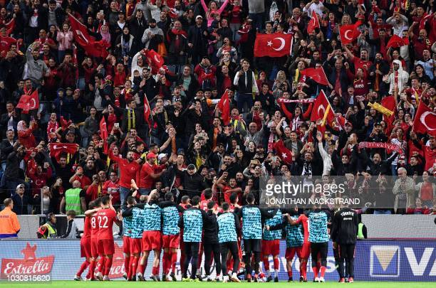 Turkish supporters celebrate with Turkey's team players after wining the UEFA Nations League football match between Sweden and Turkey at the Friends...