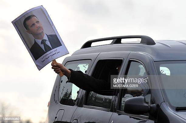A Turkish supporters of Syria's President Bashar alAssad holds a portrait of his leader from a car on January 12 2012 as activist of the group called...