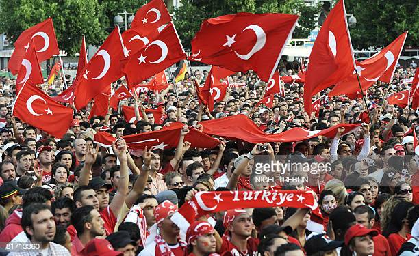 Turkish supporters wave their national flags during a public viewing session in Hanover northern Germany during the Euro 2008 championships halffinal...