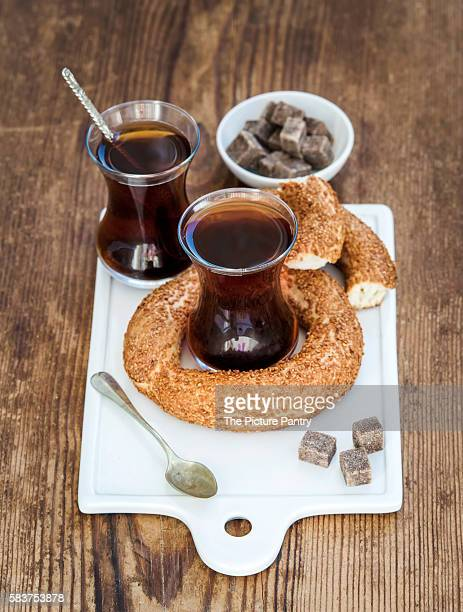 Turkish traditional black tea in a glass and turkish bagel simit on white ceramic serving board over wooden background