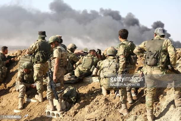 Turkish troops and Turkishbacked Syrian rebels gather outside the border town of Ras alAin on October 12 during their assault on Kurdishheld border...