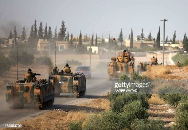 Turkish troops drive their armoured personnel carriers through the village of Qirata on the outskirts of the northern city of Manbij near the Turkish...