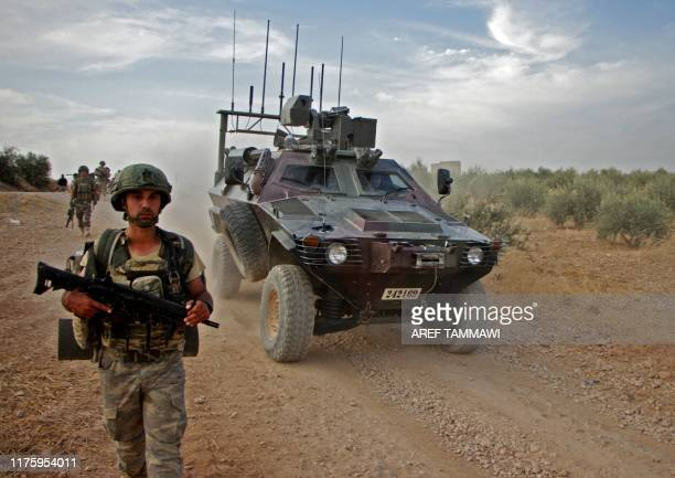 Turkish troops walk alongside an armoured personnel carrier through the town of Tukhar, north of Syria's northern city of Manbij, on October 14 as...