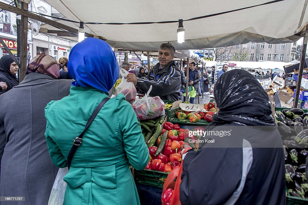 Turkish vegetable seller Halil Ilhan (3L) sells vegetables to Muslim women at the farmer's market on the Karl-Marx-Platz in Neukoelln district on November 02, 2013 in Berlin, Germany. Halil Ilhan lives for 30 years in Berlin. According to recently published statistics, 7.2 million foreigners were living in Germany by the end of 2012, which is the highest number ever recorded. Of those 80% are from countries in the European Union, while the rest come primarily from Turkey, Russia, the former Soviet states and Arab countries.