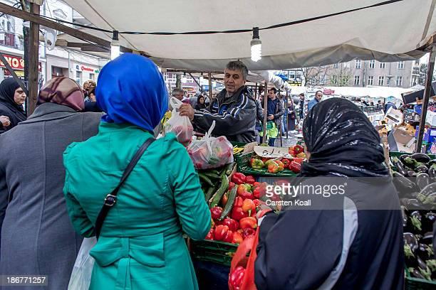 Turkish vegetable seller Halil Ilhan sells vegetables to Muslim women at the farmer's market on the KarlMarxPlatz in Neukoelln district on November...