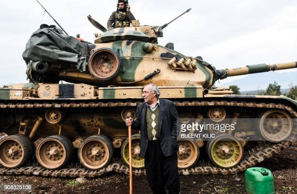 Turkish villager stands next to a Turkish army tank as soldiers gather near the Syrian border on January 21 2018 at Hassa in Hatay province Turkish...