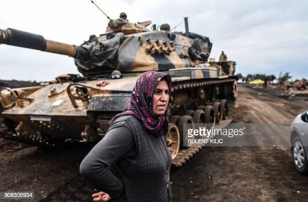 A Turkish villager stands next to Turkish army tanks as soldiers gather close to the Syrian border on January 21 2018 at Hassa in Hatay province...