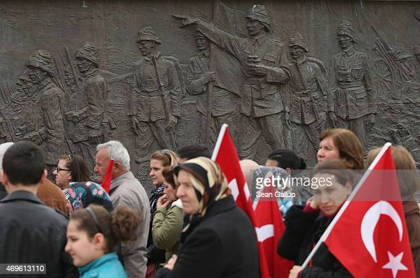 Turkish visitors holding flags walk past a relief at the Turkish 57th Infantry Regiment Memorial that shows Mustafa Kemal, then an Ottoman division...