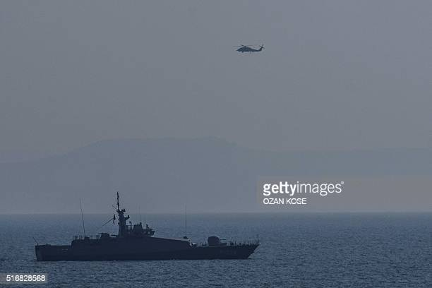 A Turkish warship and a coast guard helicopter patrol the egean sea between Turkish coast and Lesbos island on March 21 2016 at Kucukkuyu district in...
