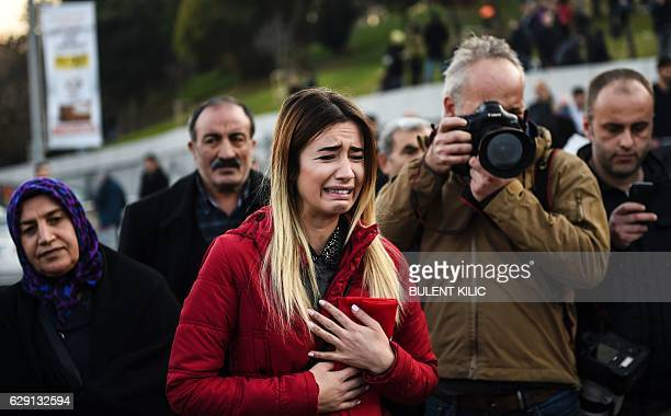 Turkish woman cries as people pay their respects outside the Vodafone Arena football stadium in Istanbul on December 11 a day after twin bombings...