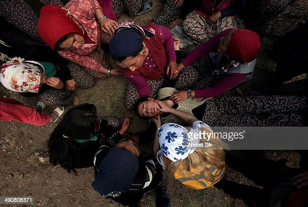 Turkish woman faints during the funeral of the the miners after a mining disaster on May 15, 2014 in Soma, a district in Turkey's western province of...