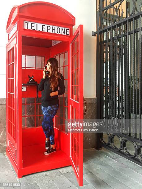 turkish woman in red telephone booth - telephone booth stock pictures, royalty-free photos & images