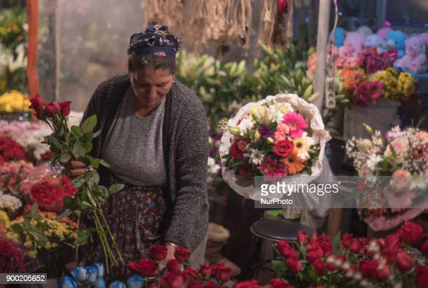 A Turkish woman sells flowers to people in Taksim Square in Istanbul on the last night of 2017