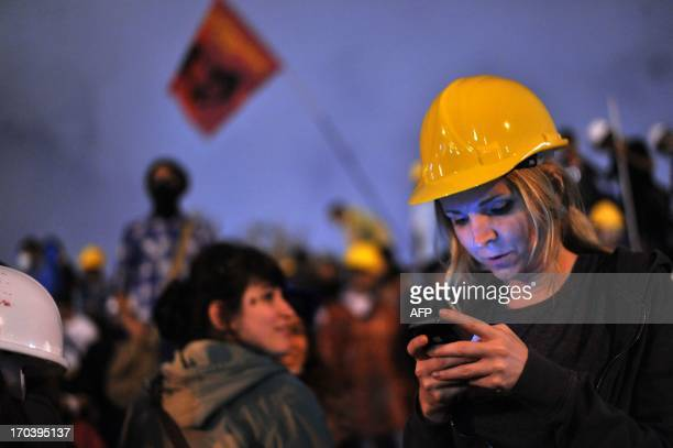 A Turkish woman using a mobile phone to read the news on social media joins demonstrators at midnight in Taksim Gezi Park on June 13 2013 in Istanbul...
