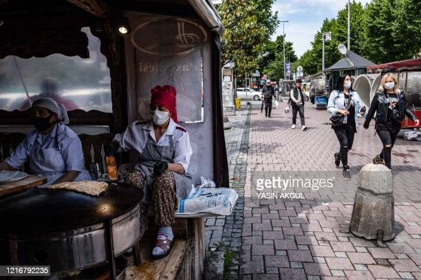 A Turkish women bakes bread on an open oven at a restaurant following its reopening on June 1 2020 in Istanbul Turkey reopened restaurants cafes on...