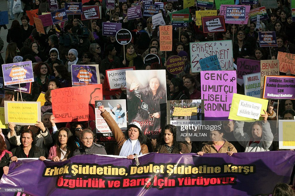 Turkish women, holding pictures of victims of domesctic violence, march on November 25, 2012 to condemn violence against women during a rally in Ankara during the International Day for the Elimination of Violence Against Women. Since 1999, the United Nations each year invites governments, international organizations and NGOs to organize activities designed to encourage the public to fight such violence. Banner reads: 'We walk against violence perpetrated by the state and men.'