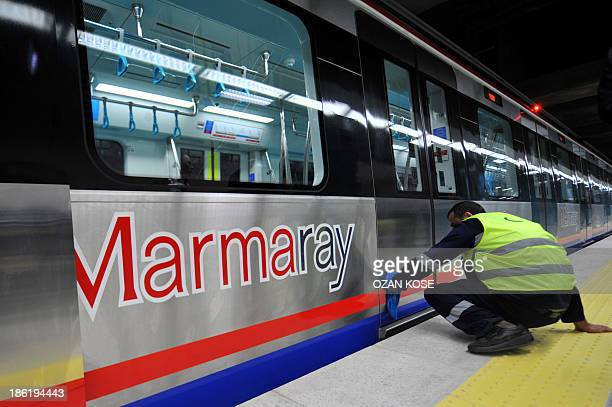 A Turkish worker cleans a train at the Uskudar Marmaray station ahead of its inauguration ceremony in Istanbul on October 29 2013 Turkey will unveil...