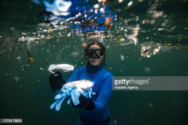 Turkish world record-holder free-diver and divers of the Underwater Federation Sahika Encumen dives amid plastic waste in Ortakoy coastline to...