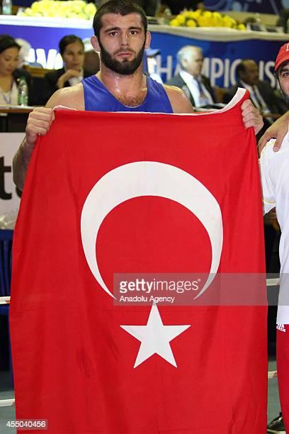 Turkish wrestler Samil Erdogan poses with Turkish flag after the 97 kg title of the United World Wrestling Freestyle Wrestling Championships in...