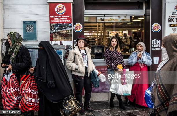 Turkish young women look on as veiled women tourists pass by in front of a Burger King fast food restaurant at the entrance of Istanbul's landmark...