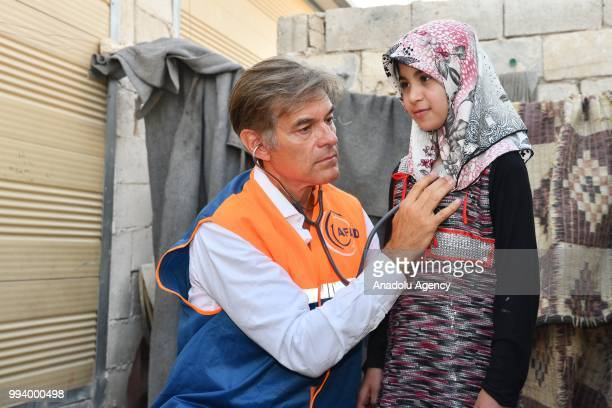 TurkishAmerican cardiothoracic surgeon Mehmet Oz examines Syrian Zeynep who has a hole in her heart during his visit in Azaz Syria on July 8 2018