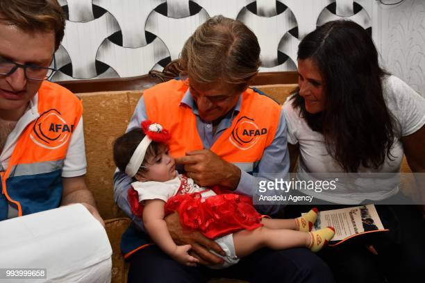 TurkishAmerican cardiothoracic surgeon Mehmet Oz takes care of a baby as he meets with Syrians during his visit to Nizip container city in Gaziantep...