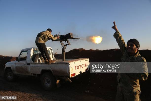 TOPSHOT Turkishbacked fighters from the Free Syrian Army stand in the Tal Malid area north of Aleppo as they fire towards Kurdish People's Protection...