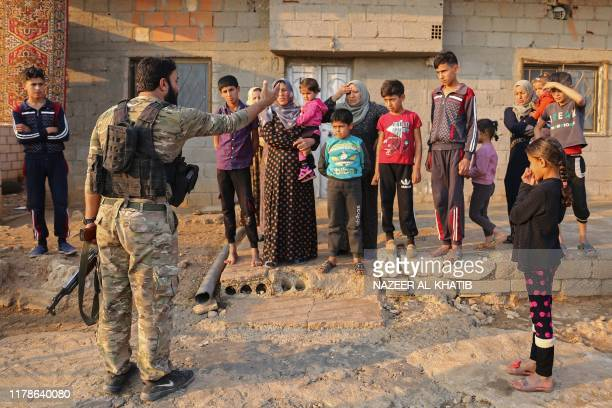 Turkishbacked fighters question residents of Jan Tamr town some 15kms east of Ras alAin city near the TurkishSyrian border after they took over the...