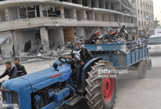 Turkishbacked Syrian Arab fighter drives towing looted items in a trailer after seizing control of the northwestern Syrian city of Afrin from the...