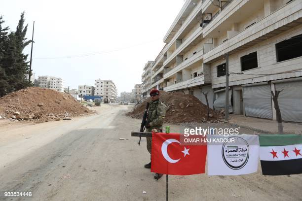 A Turkishbacked Syrian Arab fighter mans a checkpoint in the Kurdishmajority city of Afrin in northwestern Syria after seizing control of it from...