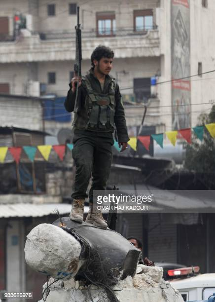 A Turkishbacked Syrian Arab fighter stands on a fallen statue of 'Kawa' the blacksmith who was a central figure in a Kurdish legend about the new...