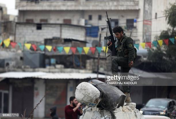 Turkishbacked Syrian Arab fighter stands on a fallen statue of 'Kawa' the blacksmith who was a central figure in a Kurdish legend about the new year...