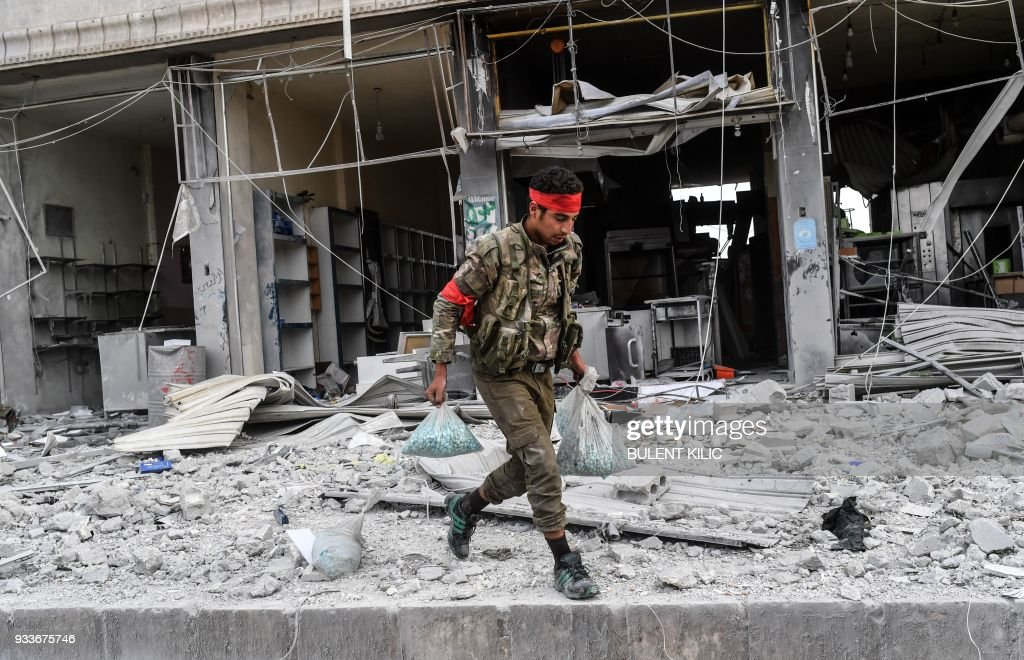 A Turkish-backed Syrian Arab fighter takes food items from a shop after seizing control of the northwestern Syrian city of Afrin from the Kurdish People's Protection Units (YPG) on March 18, 2018. In a major victory for Ankara's two-month operation against the Kurdish People's Protection Units (YPG) in northern Syria, Turkish-led forces pushed into Afrin apparently unopposed, taking up positions across the city. /